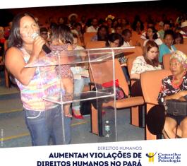 Mulher indígena com criança no colo fala em audiência pública sobre violações de direitos humanos, no Pará